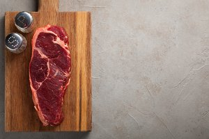 Raw beef marbled steak with vintage white Cutlery on old stone background. A piece of meat with pepper and salt on a wooden Board. Steak New York. Top view with copy space
