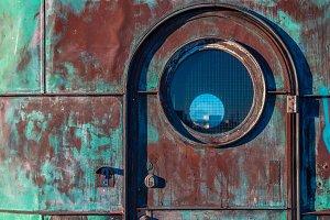Rusty green metal door with window.
