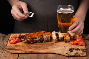 Men chef skewers with a fork ready to eat pork ribs, lying on an old wooden table. A man tries to snacks and drinks of light beer on black background