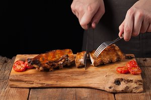 The chef cuts it with a sharp knife ready to eat pork ribs, lying on an old wooden table. A man prepares a snack to beer on a black background with copy space