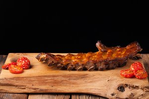 Pork ribs in barbecue sauce and honey roasted tomatoes on a wooden Board. A great snack to beer on a black background. With copy space