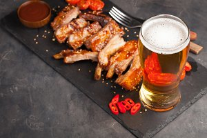 Pork ribs in barbecue sauce and honey baked tomatoes and a glass of beer on a black slate dish. A great snack to beer on a dark stone background. Top view