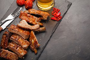 Pork ribs in barbecue sauce and honey baked tomatoes and a glass of beer on a black slate dish. A great snack to beer on a dark stone background. Top view with copy space