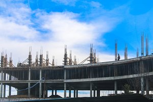 Building construction, installation of reinforcement, formwork, pouring concrete against the blue sky.