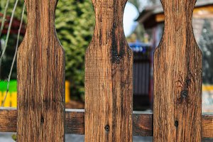 Element of a brown wooden fence consisting of separate boards with a figured end.