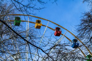 Multicolored booths of a Ferris wheel from behind trees against a blue sky.