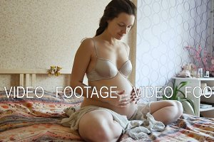 young pregnant woman touching her tummy in bedroom. she smiling, looks happy