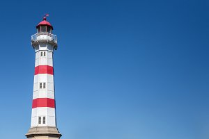 Lighthouse on blue sky background.
