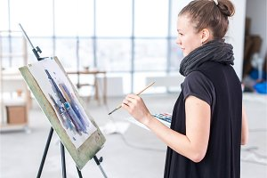 Female painter drawing in art studio using easel. Portrait of a young woman painting with aquarelle paints on white canvas.