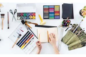 Artist drawing graphic sketch at sketchbook. Workplace, workspace. Top view photo of artistic tools lying on work-table: gouache, crayons palette and paintbrush collection.