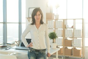 Portrait of woman standing near workplace, looking at camera.