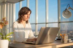 Female teleworker texting using laptop and internet, working online. Freelancer typing at home office, workplace.