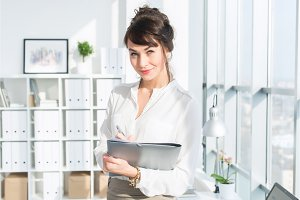 Attractive ambitious businesswoman standing in modern office, holding paper folder, looking at camera, smiling.