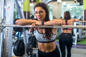 Fit woman in a gym looking at camera, resting after exercise with barbell.