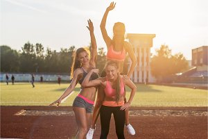 Group fit women giving piggyback ride Happy young friends enjoying a day in stadium.