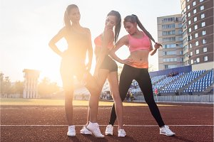 Group of fit young sportswomen standing on athletics stadium and posing.