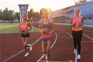 Group of women athletes running together in stadium.