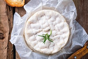 Camembert cheese with rosemary on wooden background