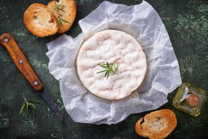 Camembert cheese with rosemary on green backgrund