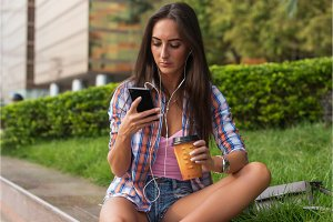 Concentrated young woman typing a text message on her mobile phone outdoors. Serious female using smartphone.