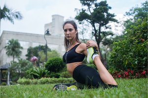 Fit young woman dressed in black sportswear doing stretching exercise for legs sitting on grass in park while listening to music in earphones.
