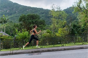 Young fit woman doing cardio exercise, listening to music, running outdoors with green mountain landscape in the background