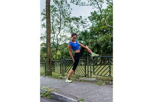 Fit girl doing stretching exercise on fence in the park. Female athlete preparing for morning workout or jogging in summer.