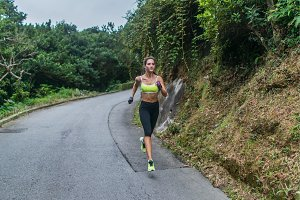 Female sport model running on road in mountains. Fitness woman training outdoors.