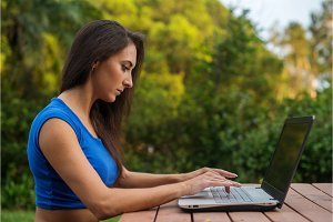 Attractive young businesswoman focused on her work looking at laptop screen sitting in park.