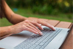 Close-up view of female hands on laptop keyboard. Student learning outdoors.