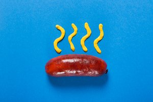 Grilled sausages prepared on grill. Blue background. Concept