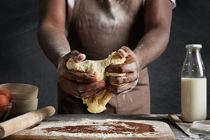 Cropped shot of hard working male cook stands in kitchen space, kneads thoroughly pastry, going to bake delicious cupcake, prepares for birthday party, isolated over chalk black studio background