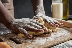Man`s hands kneads dough on wooden counter, going to roll it and make cakes, works at kitchen, isolated over black background. Talented male cook or chef bakes culinary masterpiece. Baking concept