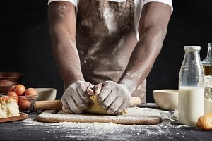 Unrecognizable dark skinned male baker kneads dough, wears apron dirty in flour, surrounded with different ingridients, wants to impress guests with delicious pie, isolated over black background