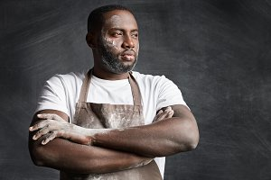 Thoughtful dark skinned male model wears apron, has dirty face and apron, looks seriously aside, keeps hands crossed, thinks what delicious to bake. Male cook poses against black background.