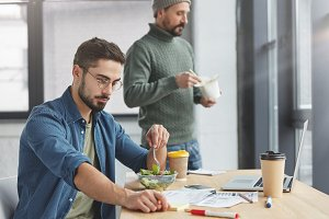 Handsome brunet male enterpreneur being vegeterian, eats healthy vegetable salad at office, studies documents attentively and his partner stands in background, eats fast food with chopsticks