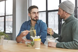 Portrait of two male colleagues have informal meeting at office, eat noodle with chopsticks and fresh vegeterian salad, have lunch at working place, discuss main issues of work. Partner`s parley