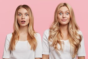 Horizontal shot of stupefied shocked two sisters stand close to each other, shocked to be hired for desired position in prosperous company, isolated over pink background. Two female companions