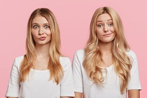 Puzzled blonde two females stand close to each other, curve lips, being uncertain about making decision, isolated over pink background. Beautiful sisters dressed casually don`t know what to do