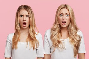 Shocked angry women keep mouth widely opened and look with stupefied expression as hear something awful and unpleasant, express negative emotions, isolated over pink background. Reaction concept