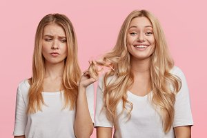 Unhappy female holds curly hair of her companion, feels envy that she has luxurious wave hair, stand together, isolated over pink background. Cheerful blonde woman spends free time with best friend