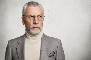 Experienced mature bearded man with grey hair, stands sideways, dressed formally, has thoughtful expression, thinks about life, isolated over white concrete background. Elderly man poses in studio