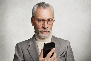 Photo of serious mature bearded handsome male dressed in grey suit, holds modern smart phone, texts messages to children and grandchildren, keeps with technology, isolated over white background