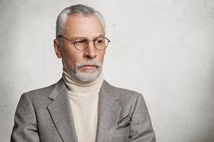 Pensive wrinkled old man with mustache and beard, wears round spectacles and formal suit, thinks about important meeting with partners, isolated over white concrete background, copy space for text