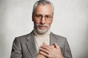 Friendly looking bearded male model wears spectacles and formal suit, keeps hands on heart, expresses great attitude to grandchildren who congratulated him with anniversary, isolated on white