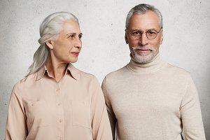 Relationship, old age and people concept. Senior couple spend time together at home, wait for children, pose against white concrete wall. Bearded elederly man in spectacles and his affectionate wife