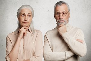 Portrait of thoughtful mature bearded male and his wife look pensively, being deep in thoughts, think about their life and achievements, isolated on white background. People, age and wisdom concept