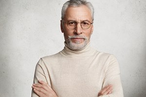 Photo of intelligent serious bearded mature man keeps hands crossed, wears light poloneck sweater and glasses, spends free time in circle of friends, isolated over white concrete background.