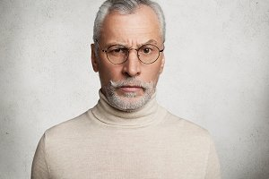 Close up portrait of serious bearded intelligent senior man wears round glasses and comfortable turtleneck sweater, raises eyebrow in bewildernent, isolated over white concrete studio background.