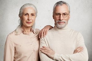 Glad grey haired wrinkled woman being pleased to meet her first love, leans at senior man`s shoulder, remember pleasant moments of their relatioship. Senior couple stand next to each other indoor